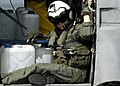 US Navy 050105-N-4166B-030 An air crewman sits in the cabin of an HH-60H Seahawk helicopter full of purified water jugs.jpg