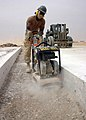US Navy 050512-N-8102P-031 Builder 3rd Class Stephen Cohen, assigned to Naval Mobile Construction Battalion Two Four, re-levels and packs the base of an airfield runway expansion joint trench at the air base in Al Asad, Iraq.jpg