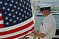 US Navy 051005-N-8937A-031 Chief Aircrew Survival Equipmentman Thomas J. Henderson, assigned to Patrol Squadron Four Seven (VP-47), raises an American flag above the USS Arizona Memorial.jpg