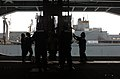 US Navy 060511-N-2959L-409 Sailors stationed aboard the Nimitz-class aircraft carrier USS Ronald Reagan (CVN 76) reach to retrieve and secure cargo from a sliding pad eye.jpg