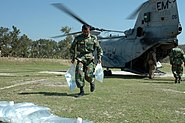 US Navy 071126-N-1831S-104 A member of the Bangladesh Army helps unload bags of purified water from a CH-46 Sea Knight assigned to the amphibious assault ship USS Kearsarge (LHD 3)