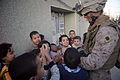 US Navy 081205-M-6687W-046 A Hospital Corpsman assigned to Company B, 1st Battalion, 4th Marine Regiment, Regimental Combat Team 1 hands out candy to Iraqi children.jpg