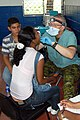 US Navy 090626-F-7885G-056 Canadian Armed Forces Maj. Don Trider, embarked aboard the Military Sealift Command hospital ship USNS Comfort (T-AH 20), examines a young woman during a Continuing Promise 2009 medical community serv.jpg