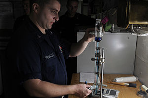 US Navy 120210-N-RG587-052 Sailors uses a titration rig to measure volumes of liquid while testing water chloride levels in the reactor labs office.jpg