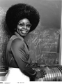 Valerie L. Thomas standing with a stack of early Landsat Computer Compatible Tapes - Original.png