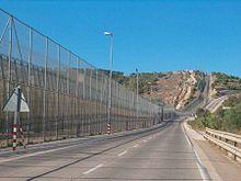 doppia recinzione a sinistra, separata da una strada per la polizia.