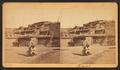 View of two Zuni individuals in front of Pueblo, by Irvine & McKenzie.png