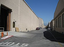 Bordering an asphalt road, receding into the distance, are two rows of large beige coloured buildings. Another beige building blocks the horizon, above which mountains are visible in the distance. The sky is blue with no clouds. Several cars are parked outside the buildings. Near the photographer, at a large open entrance to one building, the word STOP has been painted in white on the road. Next to it, a fire hydrant is visible, in front of which the words FIRE LANE are painted on the road.