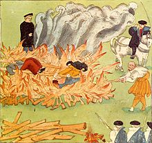 Three people lie on a large fire, watched by several men.