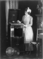 Woman, with large bow in her hair, putting needle on record on phonograph.png