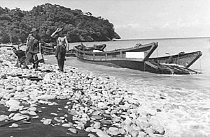 Two soldiers walk along a beach beside the wrecked remains of a number of barges