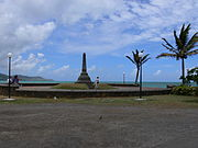A stretch of a bay. In the foreground is a gravel area in front of a large obelisk and two palm trees.