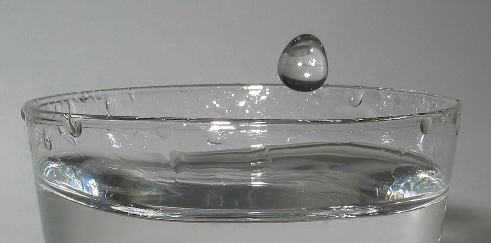 A drop of water falling towards water in a glass
