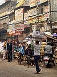 Vendeurs et enseignes le long d'une rue de terre très fréquentée à Old Delhi
