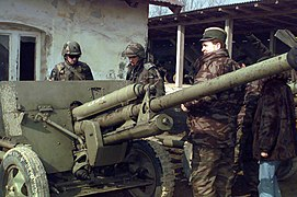 960228-A-5792S-005 - Serbian officer shows U.S. soldiers a towed ZiS-3 anti-tank gun