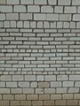 A brick wall made of bricks of different sizes.jpg