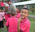 A student at Nak Ratch Boys' School in Thailand smiles for a photo as U.S. Army Pfc. Michael Brewer, a chaplain's assistant with Task Force Volunteer, Oregon Army National Guard, plays with students on 120210-Z-DQ196-001.jpg