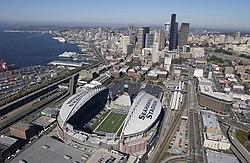 Lo stadio dal cielo in una giornata limpida.  SEAHAWKS STADIO è dipinto sul tetto parziale bianco.  Lo stadio è circondato da strade ed edifici.