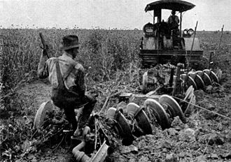 Agriculture in the United States - This photo from a 1921 encyclopedia shows a tractor plowing a crop field.
