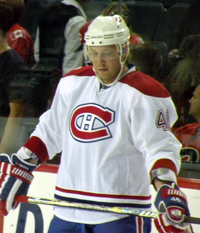 An ice hockey player standing in front of the camera. He is wearing a white helmet and a red, blue and white uniform.