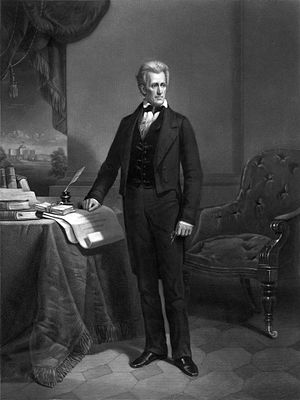 Man stands in white shirt and black pants and coat with right hand on desk and left hand at his side.