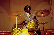 A man sit down behind a golden-colored drum kit. The man holds a pair of drumsticks and he looks concentrated while beating the cymbal at his right and the snare at the center.