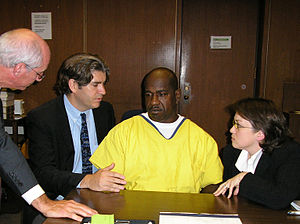 An African-American man in a yellow jumpsuit sits at a desk at the center of the photo, with a white man in his 30s in a business suit on his right, facing him. On the left and right of these two figures, respectively, are a grey-haired man in a suit, standing, and a young, dark-haired woman, crouching, both wearing glasses.