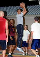 Obama holding a basketball above his head in  midair while four other players look at him. He looks toward the camera  over his right shoulder.