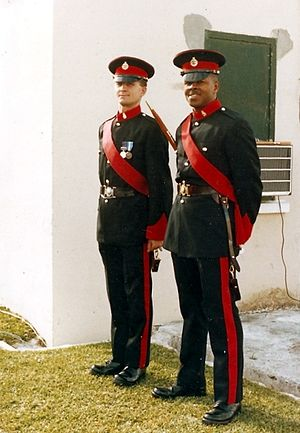 Company sergeant major - Two Bermuda Regiment warrant officers, class two. A Territorial Army company has two WO2s. On the left is a permanent staff instructor. On the right with a pace-stick, is a company sergeant major.
