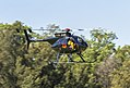 Blue Sky Helicopters (VH-MDE) Hughes 369E departing a oval at Hammondville Park.jpg