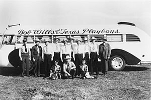 "Nine men in cowboy hats, one man in a business suit, one man in a police uniform and two young women, all in front of a bus with ""Bob Wills and his Texas Playboys"" painted on the side"