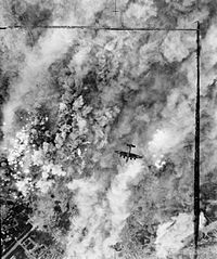 An overhead view of a bomber aircraft, flying over a pall of smoke