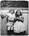 Boy and girl posed, standing, holding large cup.png