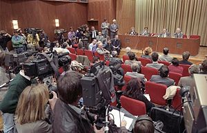 Günter Schabowski - The press conference on 9 November 1989 by Günter Schabowski (seated on stage, second from right) and other East German officials which led to the Fall of the Wall. Riccardo Ehrman is sitting on the floor of the stage with the table just behind him.