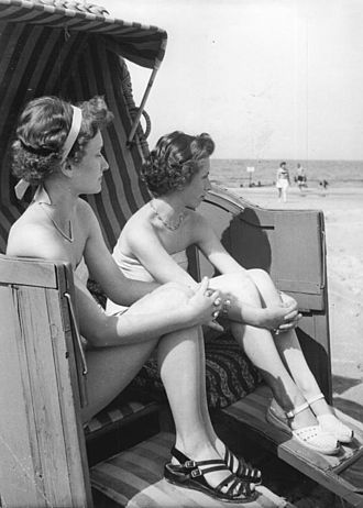 Strandkorb - Tourists occupying a strandkorb beach-chair on Darss peninsula, Germany, 1955