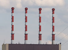 Close-up view of four red and white chimneys.