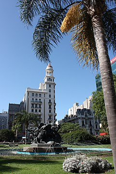 Montevideo, Piazza Fabini. All'incrocio del viale 18 de Julio e il viale del Libertador Juan A. Lavalleja. Conosciuta anche come Piazza del Entrevero (del Groviglio), per il monumento omonimo di José Belloni che domina nella piazza. Sullo sfondo il Palazzo Rex.