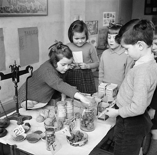 Children learning maths by adding up the costs of a shopping list in a classroom gorcery shop at Fen Ditton Junior School, Cambridgeshire in December 1944. D23629