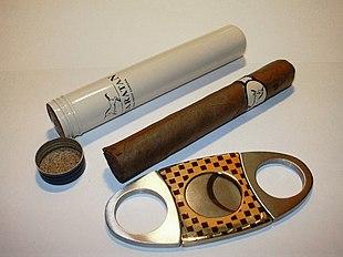 Un sigaro, il suo contenitore e un cutter a
