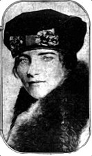 A portrait photograph of a young woman in a cloche hat and fur coat