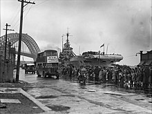 Black and white photo of a dockside scene. Buses are driving in front a crowd of people. An aircraft carrier and a bridge are visible in the background.