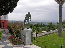 A wrestler, (one of a pair), in the Garden of Achilleion. The majestic view of the surrounding hills can be seen in the background