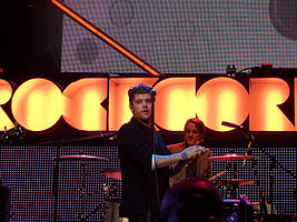 A thirty-six year-old man is shown in three-quarter view. He is standing centre-stage, half-turned with hands clapped together. He is partly obscured by a microphone stand in front. Behind him is a drummer at his kit. Beyond that is the lighting, which includes the partly spelled letters R-O-C-K-C-O-R in large orange-yellow.