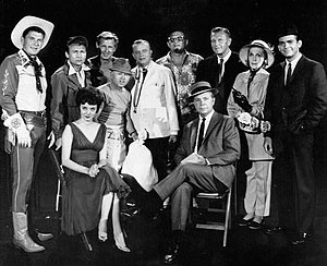"Carolyn Jones - Guest stars for the 1961 premiere episode of The Dick Powell Show, ""Who Killed Julie Greer?"".  Standing, from left: Ronald Reagan, Nick Adams, Lloyd Bridges, Mickey Rooney, Edgar Bergen, Jack Carson, Ralph Bellamy, Kay Thompson, Dean Jones. Seated, from left, Carolyn Jones and Dick Powell."
