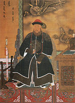 Three-quarter painted portrait of a thickly bearded man wearing a red hat adorned with a peacock feather and dressed with a long dark robe with dragon patterns. Clockwise from bottom left to bottom right, he is surrounded by a sheathed sword mounted on a wooden display, Manchu writing on the wall, a three-clawed dragon and a five-clawed dragon (also printed on the wall), and a wooden desk with an incense burner and a book on it.
