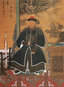Three-quarter painted portrait of a thickly bearded man wearing a red hat adorned with a peacock feather and dressed with a dark long robe with dragon patterns. Clockwise from bottom left to bottom right, he is surrounded by a sheated sword mounted on a wooden display, Manchu writing on the wall, a three-clawed dragon and a five-clawed dragon (also printed on the wall), and a wooden desk with an incense burner and a book on it.