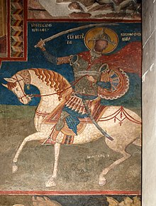 Medieval fresco of an armoured saint on a white horse swinging a sword