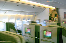 Airline business class cabin. Seats arranged in twos, with forward display screens.