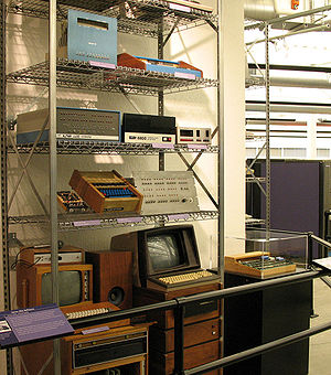 Microcomputer - A collection of early microcomputers, including a Processor Technology SOL-20 (top shelf, right), an MITS Altair 8800 (second shelf, left), a TV Typewriter (third shelf, center), and an Apple I in the case at far right.