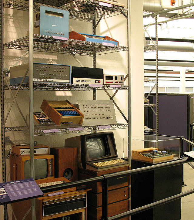 A collection of early microcomputers, including a Processor Technology SOL-20 (top shelf, right), an MITS Altair 8800 (second shelf, left), a TV Typewriter (third shelf, center), and an Apple I in the case at far right. Early Personal Computers.jpg